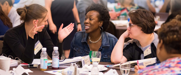 This image shows a group of four women interacting at a table during a professional learning event.