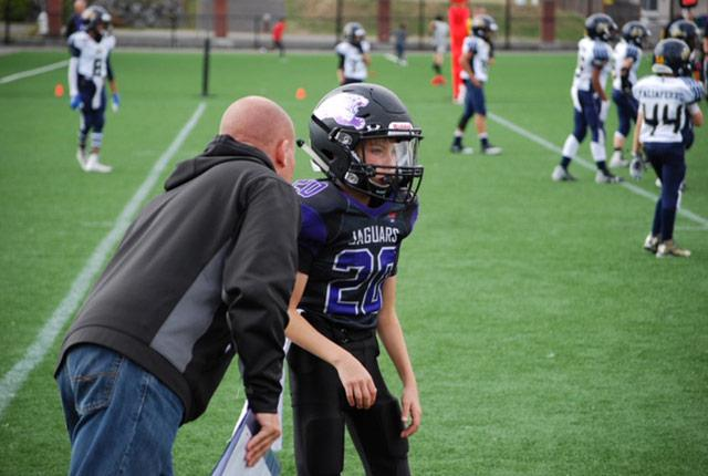 Coach leans in to speak to a youth football player wearing a helmet.