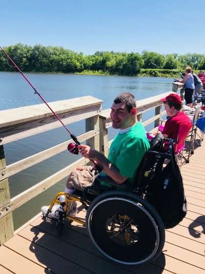 Man smiling and fishing from his wheelchair with others in a row behind him fishing also.