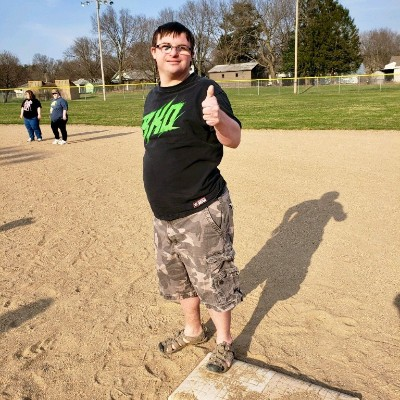 Kickball participant standing at first base giving a thumbs up.