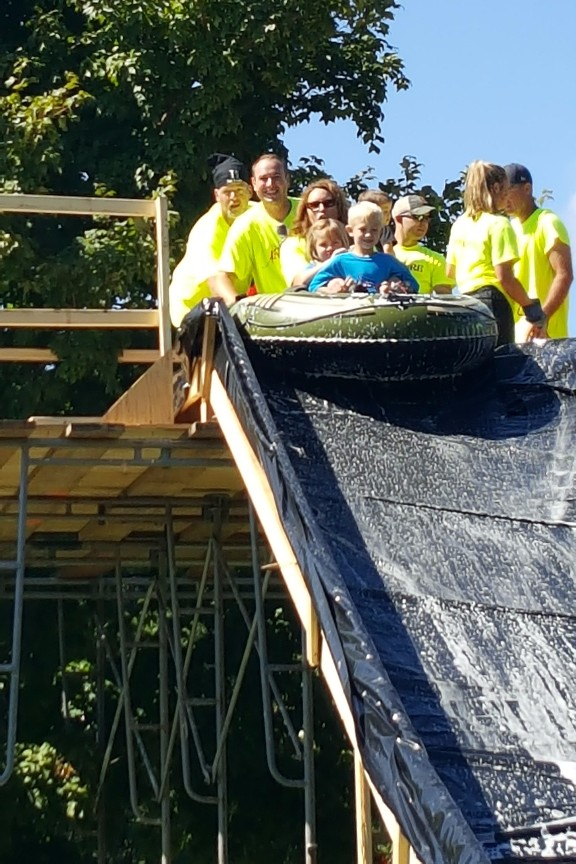 Volunteers assisting a group on the slip-n-slide of the obstacle course.