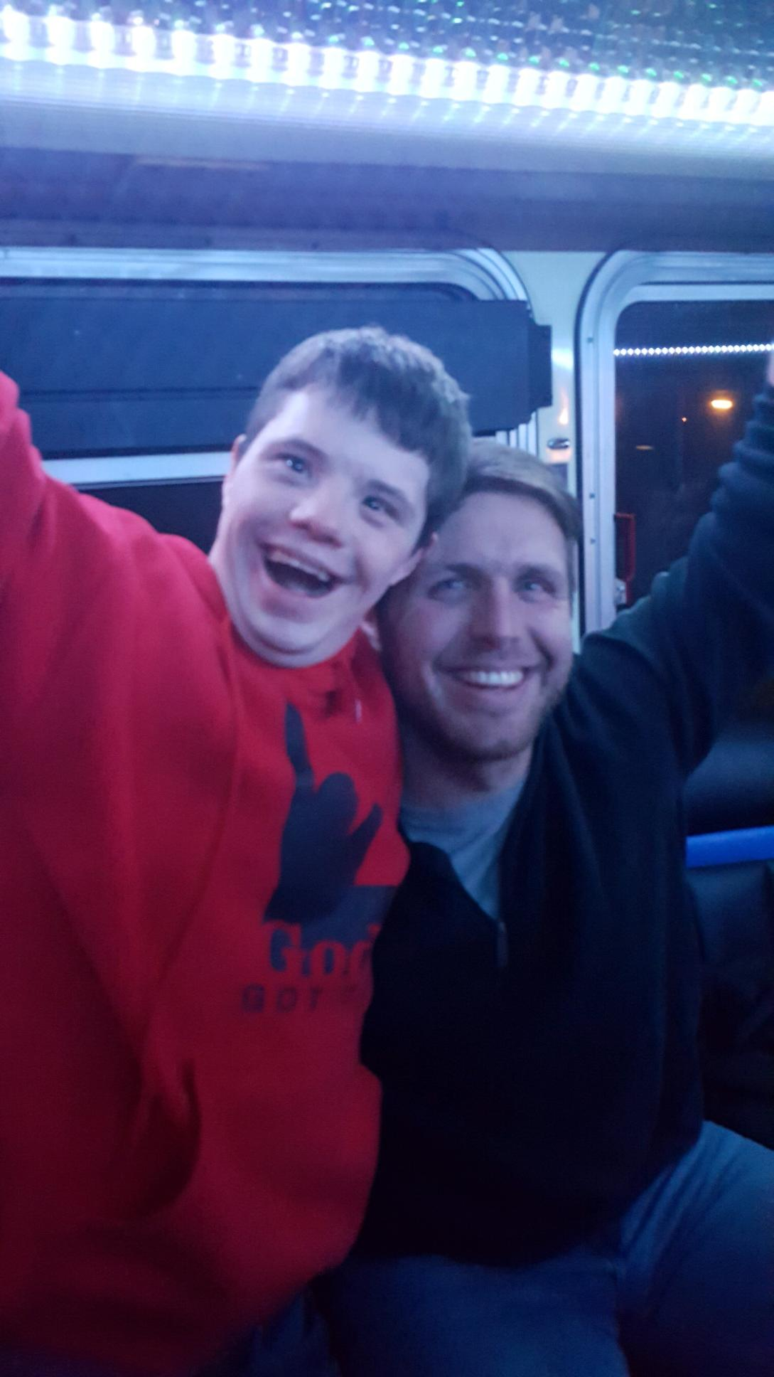 Two men with hug smiles inside a bus.