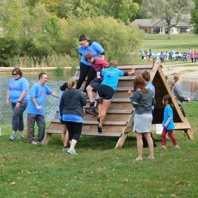 Volunteers support participant in coming down from the A-frame on the obstacle course.