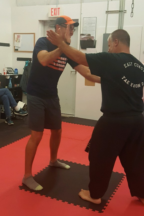 Tae Kwon Do participant practices striking with instructor.