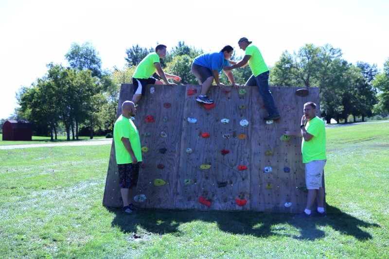 Volunteers assisting a participant on the climbing wall.