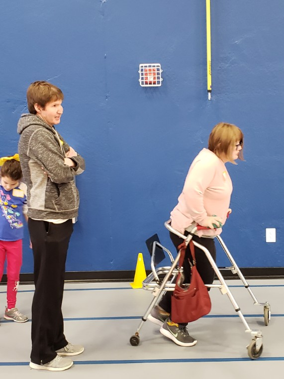participant using a walker to move forward in gym