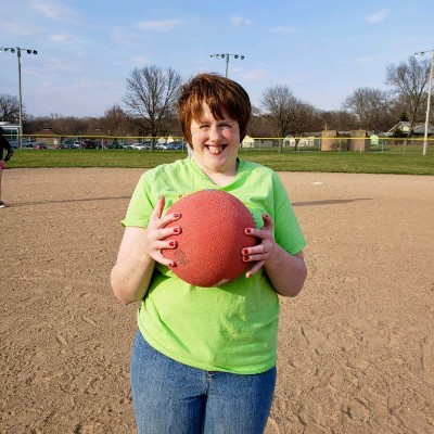 Girl holds kickball with a big smile on her face.