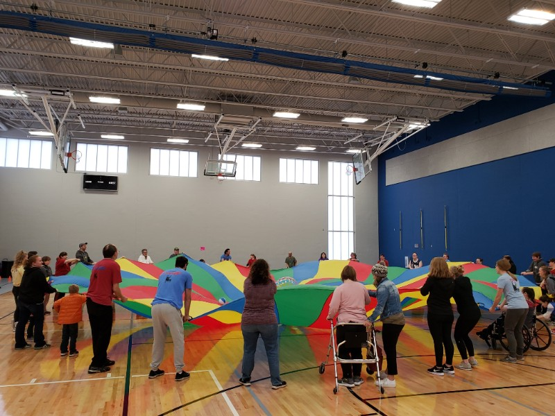 Large group of participants in a gym holding a large parachute