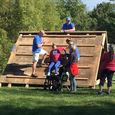 Volunteers support participant in coming down from the A-frame on the obstacle course and into her wheelchair.