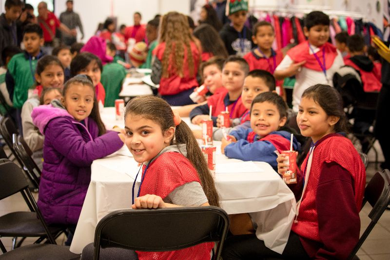 Students eating lunch at Christmas 4 Kids event