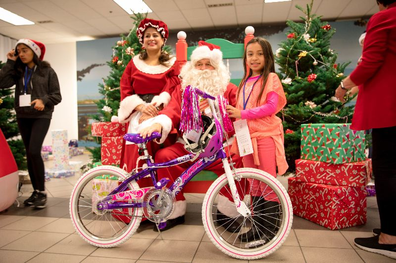 Students receives bike from Santa at Christmas 4 Kids event