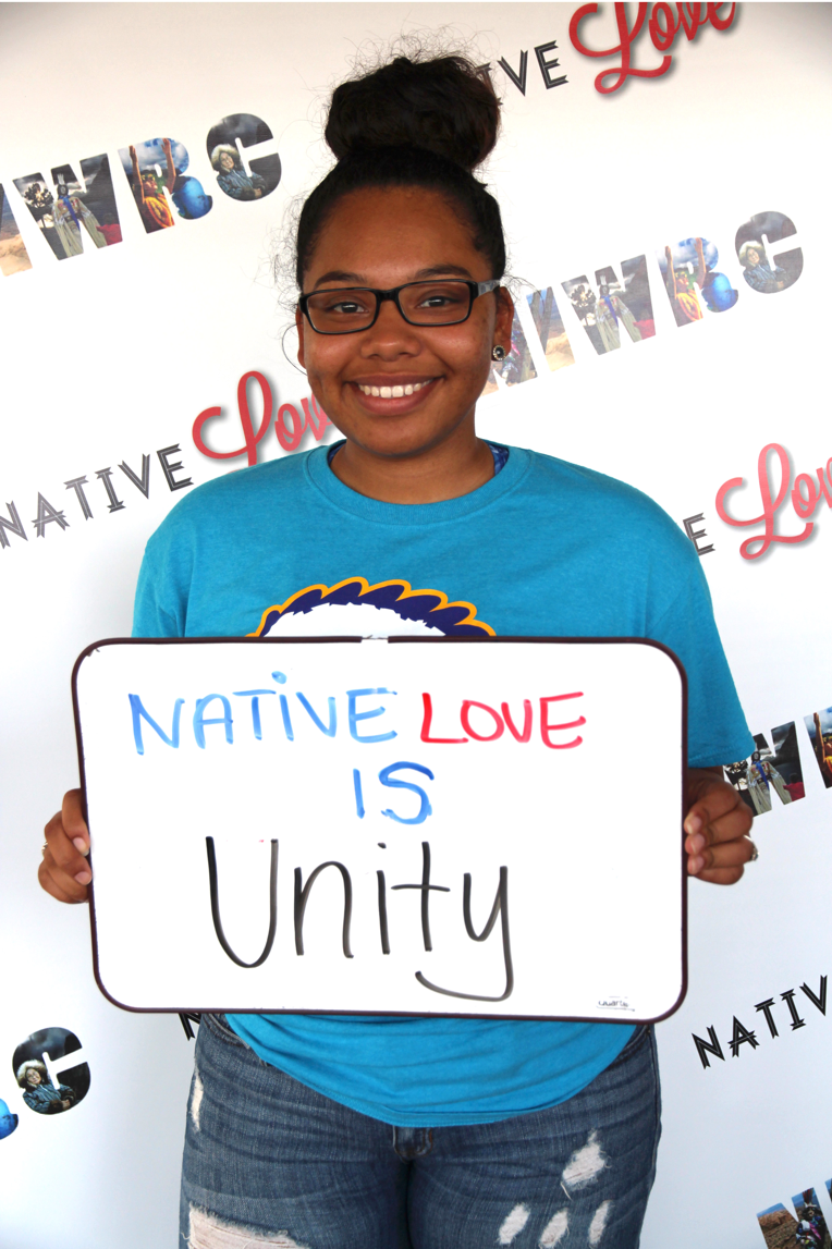 "young woman holding sign that reads ""native love is unity"""