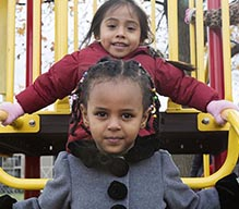 Two young girls standing on playground equipment.