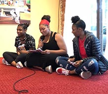 three girls sitting together while one speaks into a microphone