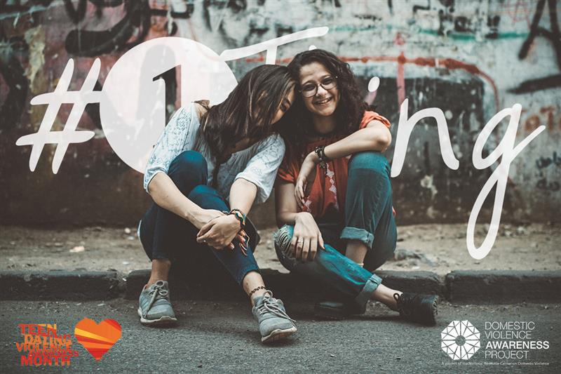 Two youth women sitting on the curb next to each other. #1Thing logo behind them.