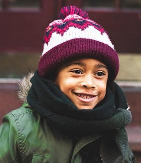Young child wearing a winter hat & scarf