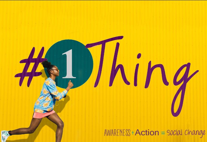 girl running in front of yellow wall with #1Thing logo
