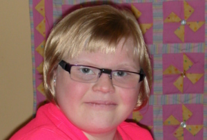 teenage girl with a round face, glasses, and short blond hair