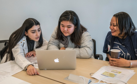 Young women work on a laptop computer as Berkeley Lab mentor looks on.