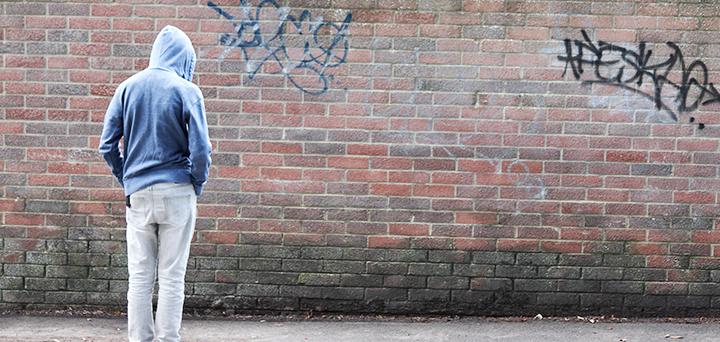 Photo of a person standing, wearing a hooded sweatshirt and facing a brick wall covered in graffiti.