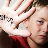Young boy with Stop written on the palm of his hand
