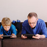 Image of man and child using technology alongside each other