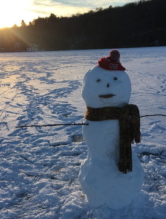A handsome snowman with an Overbrook School for the Blind hat sits on a frozen lake with the sun setting behind him.