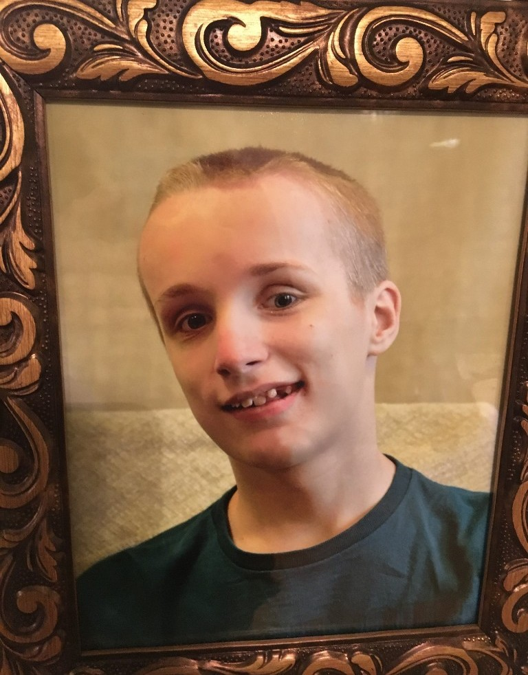 A smiling portrait of Joey P. a 13 year old boy with short blond hair.