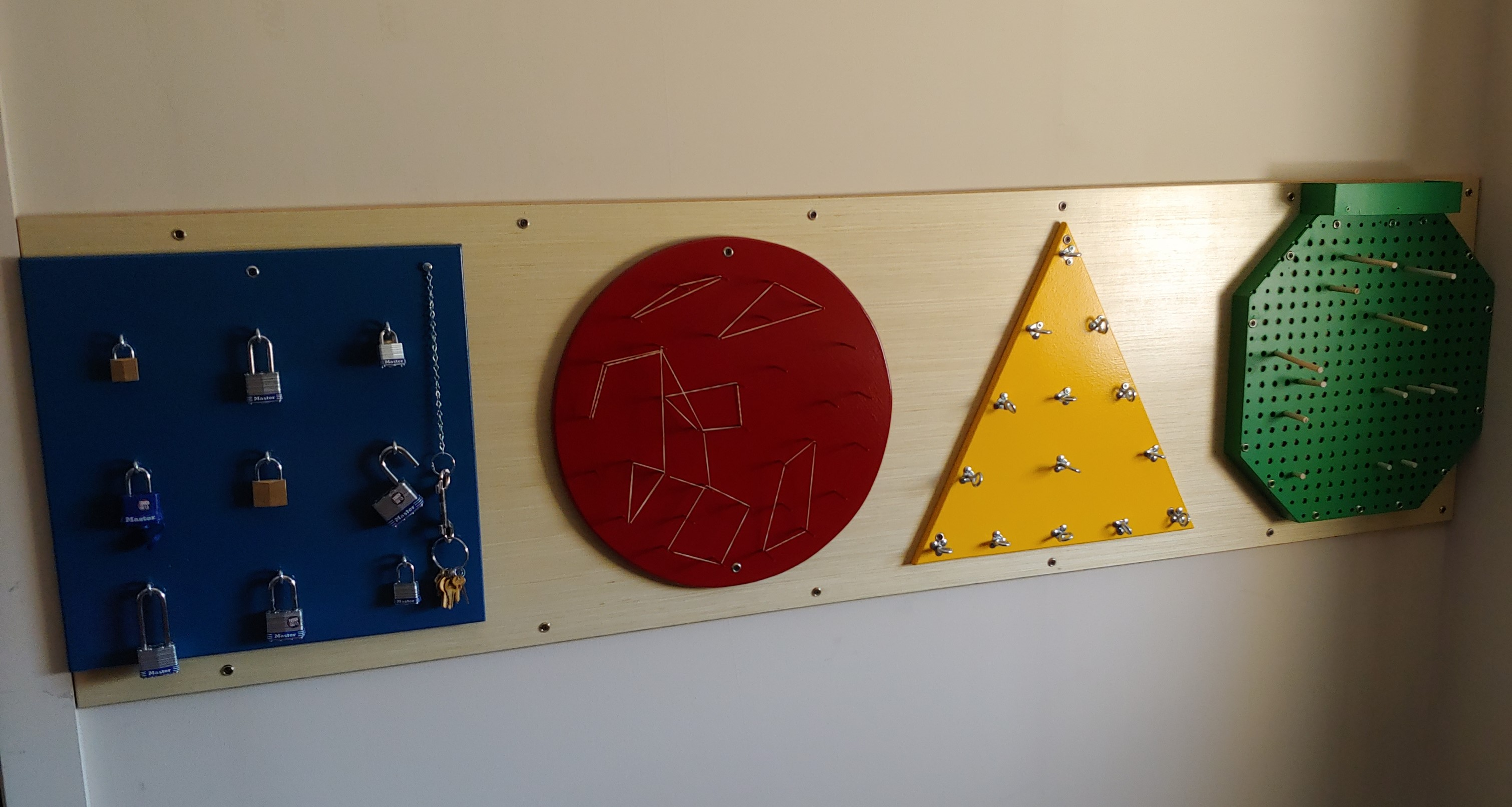 Busy Wall: 4 shapes affixed to the wall, about 1 foot by 1 foot large, each containing an activity.  A blue square holds 9 padlocks with keys, a red circle has nails where rubber bands can be placed in different shapes, a yellow triangle holds large screws that can be moved in and out, and a green hexagon has holes and pegs to rearrange.