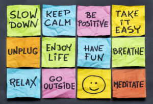 "A collection of Post It notes which read, ""Slow Down,"" ""Keep Calm,"" ""Be Positive,"" ""Take it Easy,"" ""Unplug,"" ""Enjoy Life,"" ""Have Fun,"" ""Breath,"" ""Relax,"" ""Go Outside,"" smiley face, and ""Meditate."""