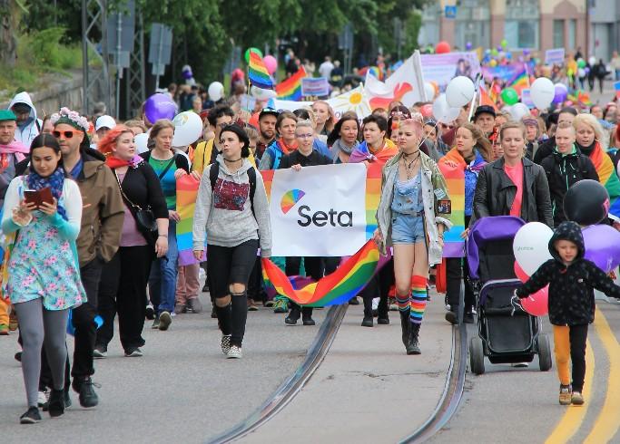 Kuvassa on satoja ihmisiä Helsinki Pride marssilla 2017. Keskellä kuvaa on Setan nimi banderollissa. Kulkueessa on lapsia, nuoria ja aikuisia, ilmapalloja ja sateenkaarilippuja.
