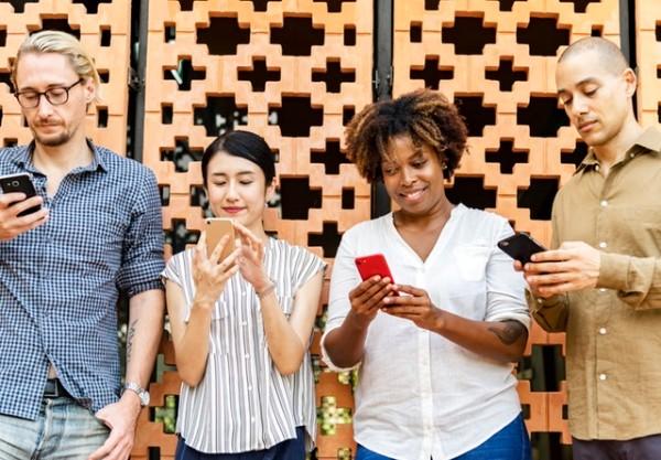 Image of women and men looking at smartphones