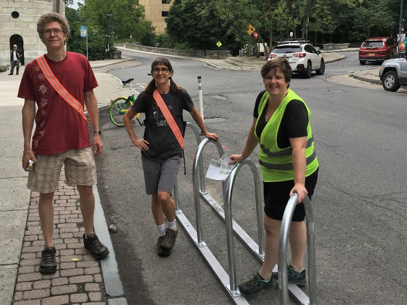 Three BWT volunteers installing the temporary bike corral on College Ave by Sheldon Court.