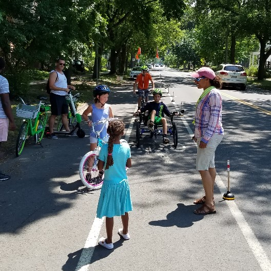 People of all ages enjoying a temporary protected bike lane at the Fall Creek Bike Party.