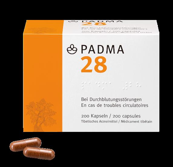 Eine Schachtel des Arzneimittels Padma 28. Davor liegen zwei Kapseln