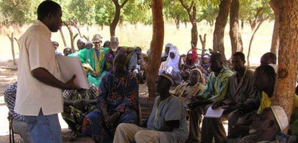 Image showing people from a village in Mali listen to a man providing legal literacy training to raise their awareness on the law and land rights.