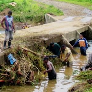 People clearing flood damage in Fiji