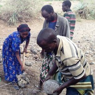 Members of a community risk reduction committee fill gabion bags with stones to prevent flood damage to farm land in Ethiopia (Photo: USAID/CRS, Creative Commons via Flickr)