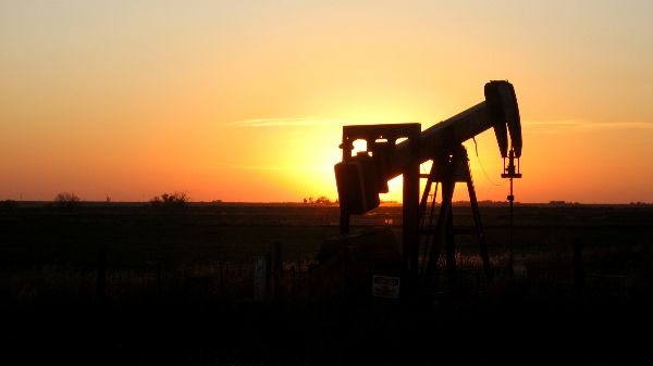 Photo: An oil rig silhouetted at sunset in the Oklahoma Panhandle (Credit: Gina Dittmer, Creative Commons)