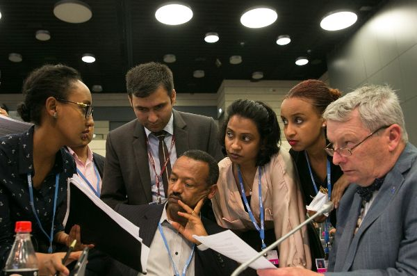 Gebru Jember Endalew, the former chair of the Least Developed Countries Group, and LDC advisors including IIED's Achala Abeysinghe discuss the Paris Agreement text in Bonn (Photo: IISD/ENB   Kiara Worth)