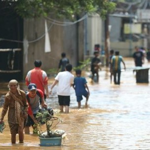 Citizens wade through floods in Bandung City in September 2018 due to the overflow of the Renggong River. In addition to more natural disasters, a warming world will result in huge changes to normal life, and affect the poorest countries worst (Photo: World Meteorological Organisation, Creative Commons, via Flickr)