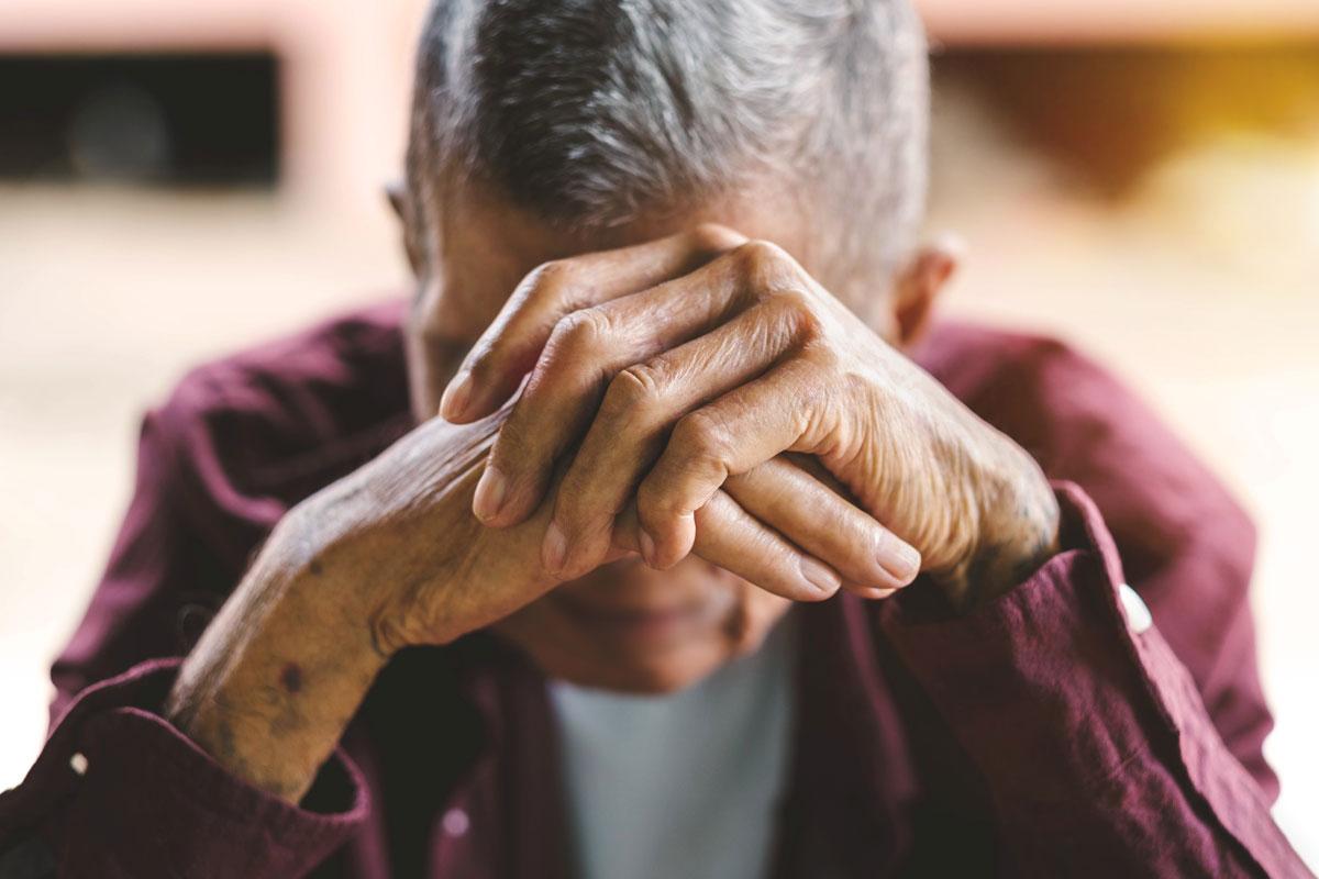 elderly man with head lowered