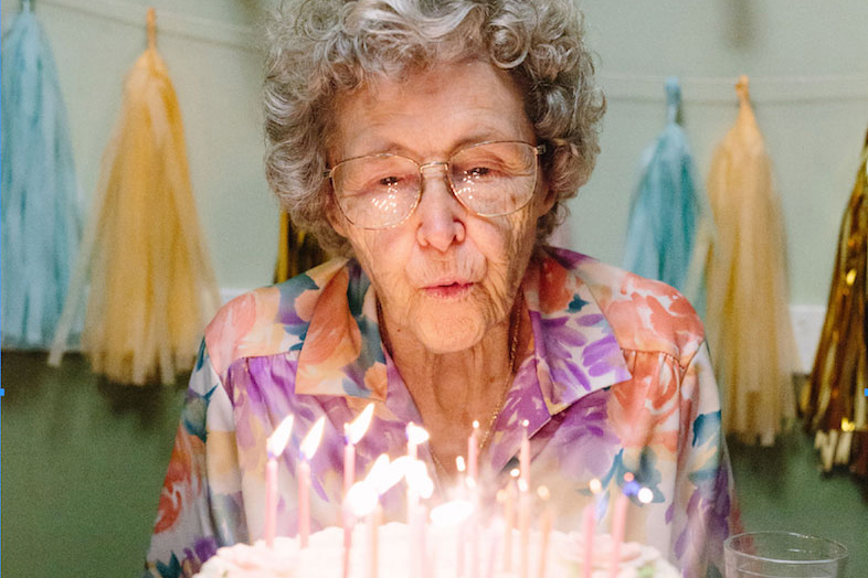 senior woman blowing out birthday candles