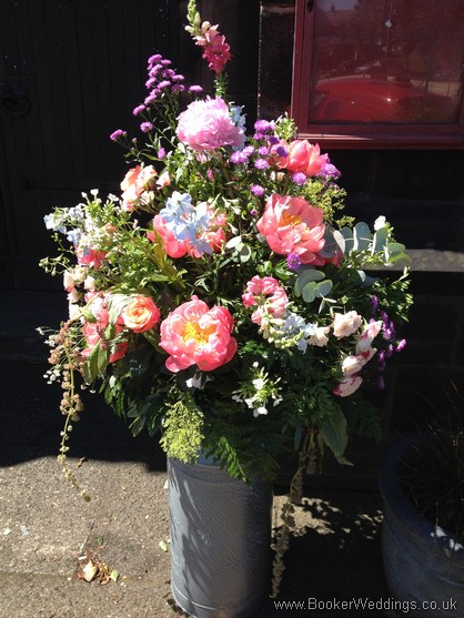 Large bright colourful just picked country style milk churn arrangement for entrance to St Barnabus Church