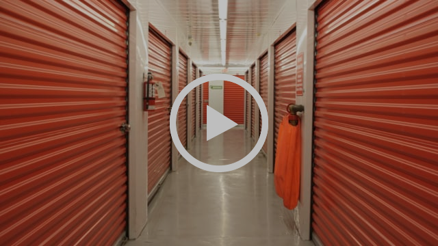 This image shows the hallway of a storage facility in which there are several locker doors.