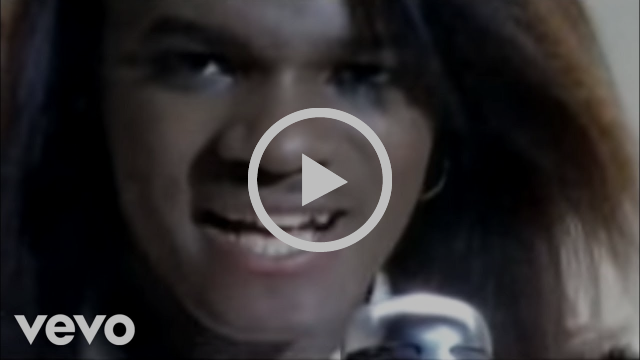 Jermaine Stewart. Black man with a blow out sings into a silver microphone.