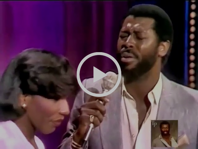 Stephanie Mills and Teddy Pendergrass looking sharp as shit singing into mics on a stage.